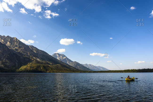 Landscape with mountain and kayaking man on lake, Grand Tetons National Park, Wyoming, USA?