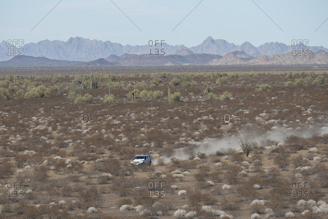Jeep driving along path in barren desert landscape, Sonora, Mexico