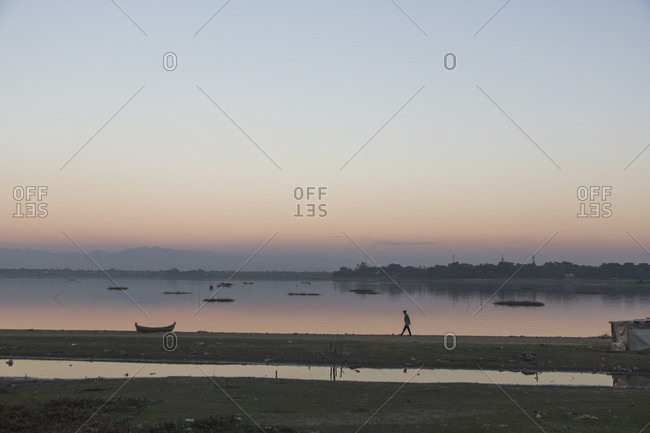 Clear sky over silhouette of person walking along lakeshore at dusk, Mandalay, Mandalay District, Myanmar