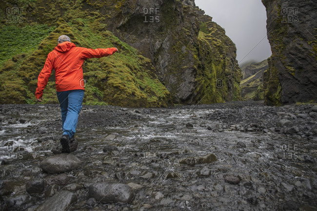 Man balancing over rocks to cross river at Stakholtsgja Canyon in Thorsmork valley at cloudy day, Thorsmork, Sudurland, Iceland