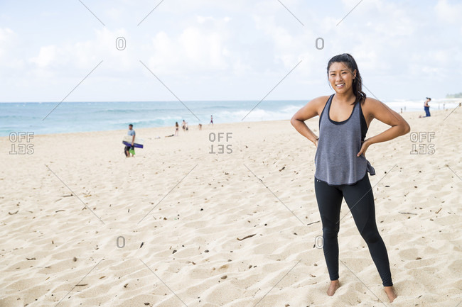 Strong young woman standing on sandy beach on North Shore of Oahu at daytime, Hawaii, USA