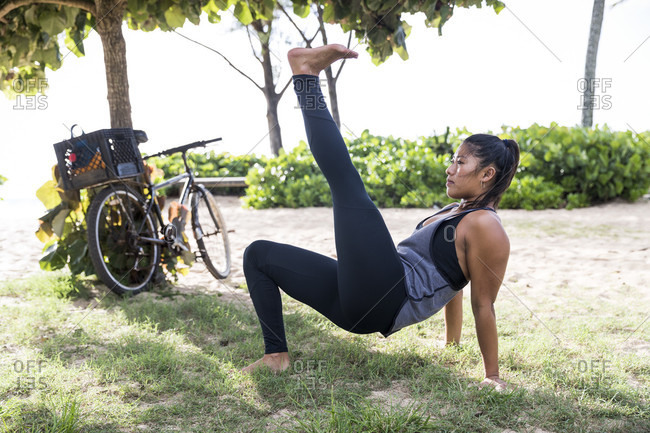 Strong young woman exercises on grass in park on North Shore of Oahu at daytime, Hawaii, USA