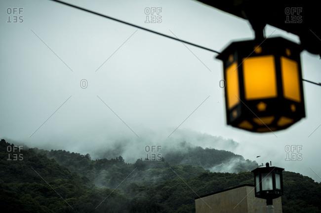 Dim lantern hanging from train platform with misty mountains in background, Arashiyama, Kyoto, Japan