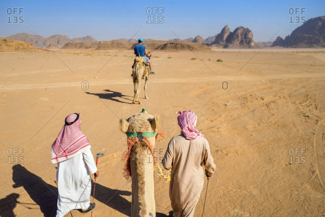 First person perspective riding camel through desert of Wadi Rum protected desert wilderness in southern Jordan, with sandstone mountains and man riding camel in distance, Wadi Rum Village, Jordan