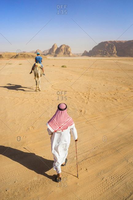 View of man in Arabic clothing walking through desert of Wadi Rum in southern Jordan, with sandstone mountains and man riding camel in distance, Wadi Rum Village, Jordan
