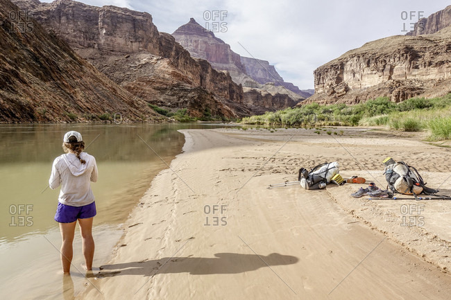 Taking break from hot day of hiking in Grand Canyon, young woman cooling off with her feet immersed in Colorado River, Grand Canyon, Arizona, USA