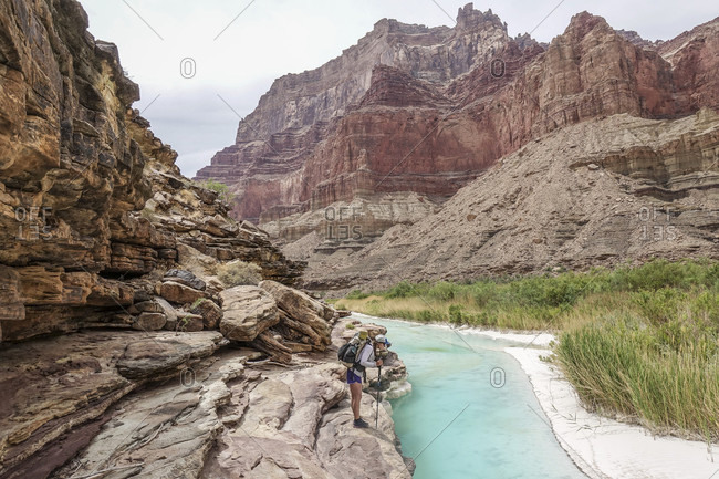 Landscape with young woman standing on rock formation and contemplating?turquoise water of Little Colorado River near its confluence with Colorado deep down in Grand Canyon, Grand Canyon, Arizona, USA
