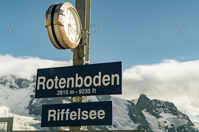 Riterboden, Riffelsee gondola station with clock and information plates in front of snowy Gorengrat summit, ?Zermatt, ?Valais, Switzerland