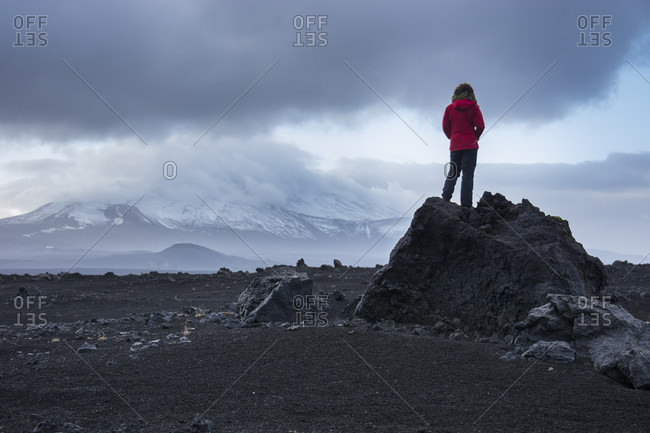A young adventurous woman with a red jacket, stands on top of a black, volcanic rock as she stares off into the distance, gazing at the snowy mountain covered by clouds, Hekla, in Iceland