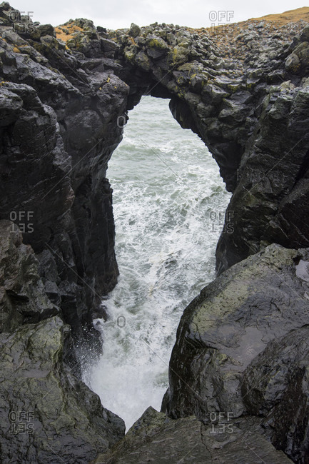 Natural arch over splashing coastal waters at Snaefellsnes peninsula, Arnastapi, Iceland