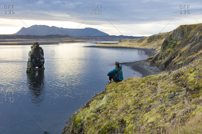 Female hiker sitting at edge of coastal cliff and looking at rock formation, Hvitserkur, Iceland