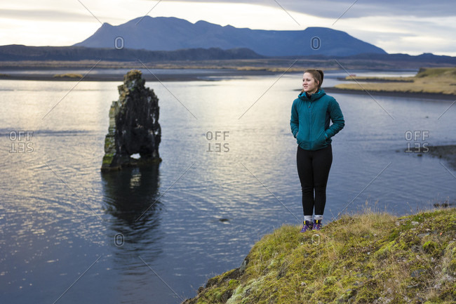 Female hiker standing at edge of coastal cliff with rock formation in background, Hvitserkur, Iceland