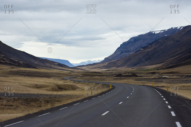 Empty Ring Road highway winding across mountain valley, Hringvegur, Iceland
