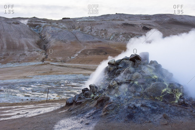 An active steam spring spits out sulphur and other poisonous gases in the form of fumes, which have coloured the soil around it blue and bright yellow, as well as Namafjall mountain which can be seen in the background, in Hverar??ndor Hverir Geothermal Area at Namaskard Pass, North Iceland.