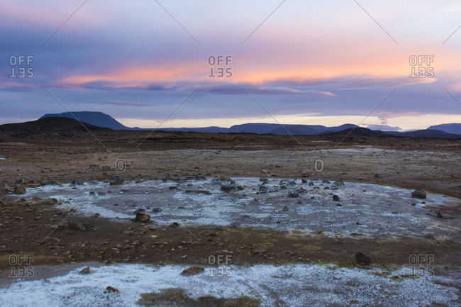 Blue coloured minerals, left behind by volcanic mud puddles and fumes, contrast with the orange coloured sky in Hverar??ndor Hverir Geothermal Area at Namaskard Pass, North Iceland.