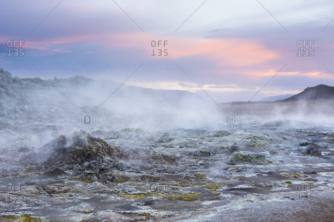 A boiling hot mud puddle spits out steam and poisonous fumes, which in turn have coloured the soil around it blue and bright yellow, while the sunset colours a cloud orange, in Hverar??ndor Hverir Geothermal Area at Namaskard Pass, North Iceland.