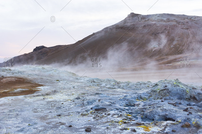 A boiling hot mud puddle spits out steam and poisonous fumes, which in turn have coloured the soil around it blue and bright yellow, as well as Namafjall mountain which can be seen in the background, in Hverar??ndor Hverir Geothermal Area at Namaskard Pass, North Iceland.