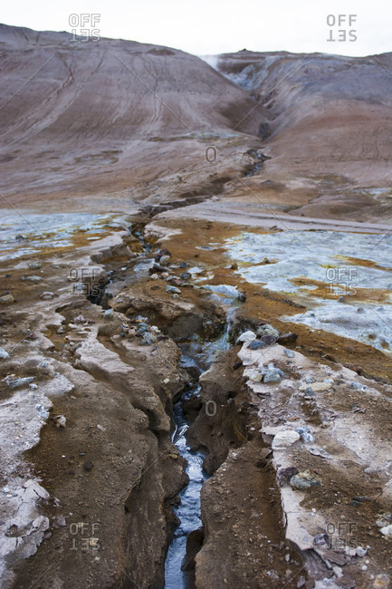 A cobalt coloured stream flows down from Namafjall mountain through the Hverar??ndor Hverir Geothermal Area, traversing brightly coloured minerals and soil at Namaskard Pass, North Iceland.