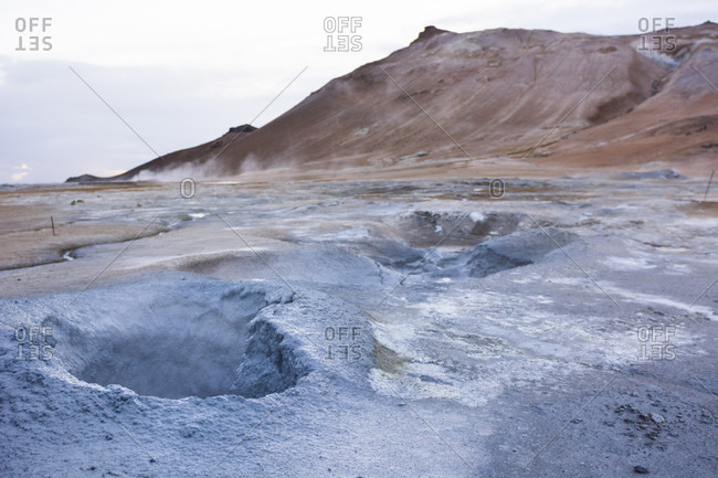 A series of boiling hot blue coloured mud puddles spit out  steam, sulphur and other poisonous gases , which have coloured the soil around it blue and bright yellow, as well as Namafjall mountain which can be seen in the background, in Hverar??ndor Hverir Geothermal Area at Namaskard Pass, North Iceland.