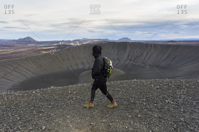 A young woman dressed in black and wearing boots walks along the ridge of the Hverfjall crater with steam rising in the volcanic background.