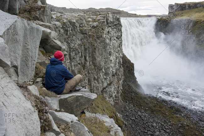 A young man wearing a blue jacket and a red beanie sits down on a rock on the cliff face as he admires Dettifoss waterfall in North Iceland.