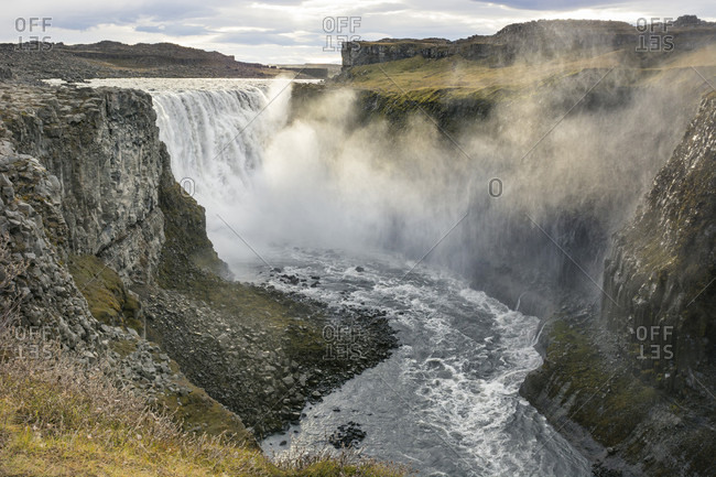 The evening sun colours the mist of Dettifoss waterfall golden as it sprays the canyon around it, in North Iceland.