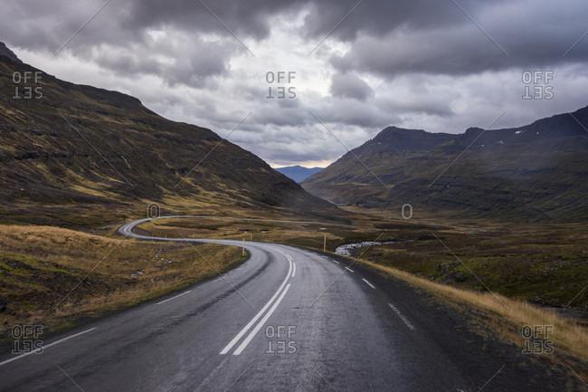 Cloudy sky over empty Seydisfjardarvegur highway winding between grassy mountains, Iceland
