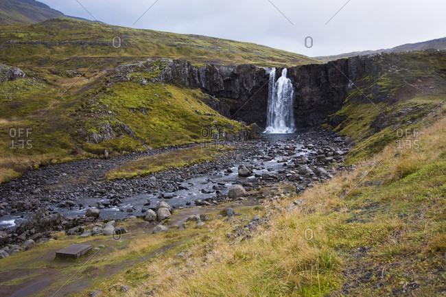 Scenic view of splashing Gufufoss waterfall and surrounding grassy landscape, Iceland