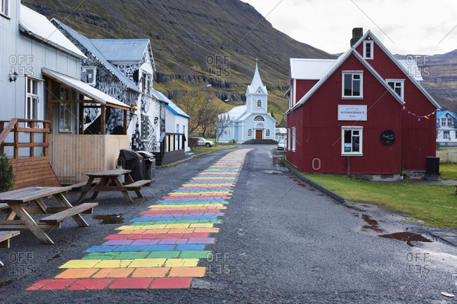 October 24, 2016: Rainbow colored brick road between houses leading to small church at edge of town, Seydisfjordur, Iceland