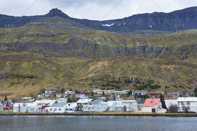 October 24, 2016: Scenic view of small coastal town along shore of oceanic fjord with grassy mountain in background, Seydisfjordur, Iceland