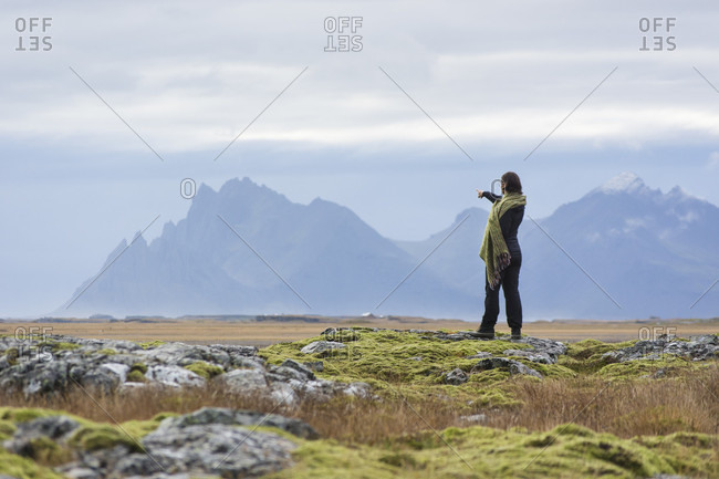 A young woman wearing a green, long scarf points at the rugged mountain of Vesturhorn with Vestrahorn on the side, in East Iceland, Hringvegur, East Iceland, Iceland