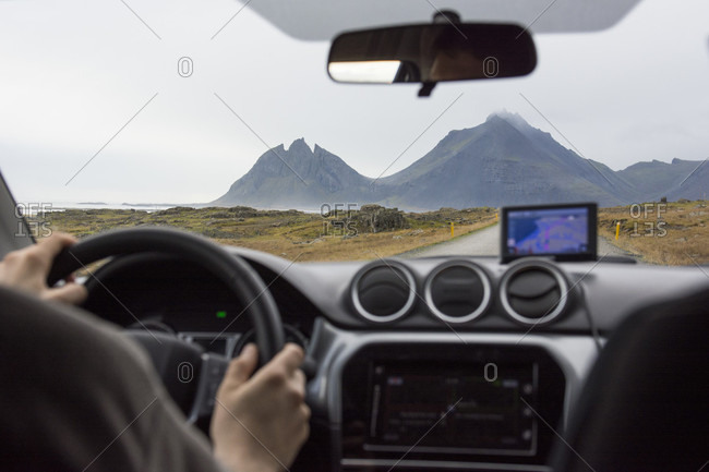 A young man drives a car with a gps in the Ring Road, towards the mountains Vesturhorn and Vestrahorn in East Iceland, Hringvegur, East Iceland, Iceland
