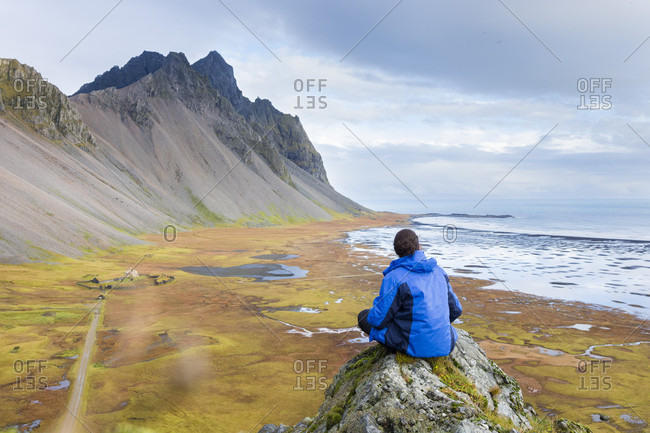 Young man wearing a blue jacket sits on a moss covered rock as he admires the landscape of Stokksnes beach, with the Viking village movie set, ocean and mountains, Stokksnes, East Iceland, Iceland