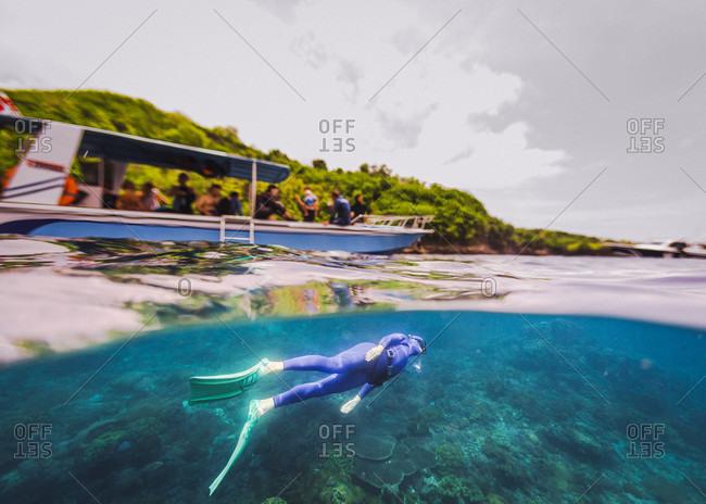 Freediver hanging underwater under tour boat full of tourists, Nusapenida, Bali, Indonesia