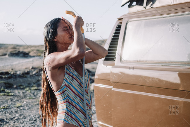 Girl takes shower out of her vintage camper van, Tenerife, Canary Islands, Spain