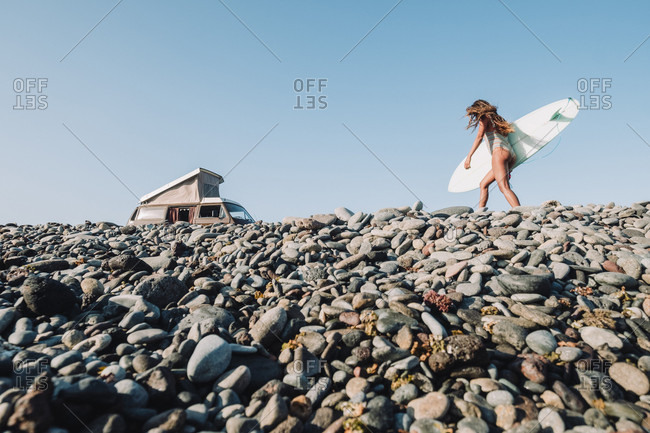 Female surfer walks back to her vintage camper van on cobblestone beach, Tenerife, Canary Islands, Spain