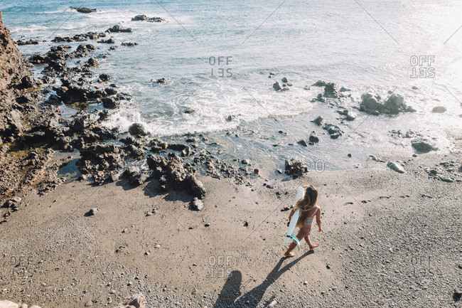 Aerial view of female surfer walking with her surfboard on beach, Tenerife, Canary Islands, Spain