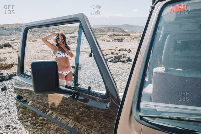 Woman in bikini taking picture through window of vintage camper van at daytime, Tenerife, Canary Islands, Spain
