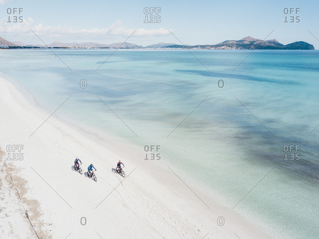 Aerial view of cyclists riding mountain bikes on white sand beach, Mallorca, Balearic Islands, Spain