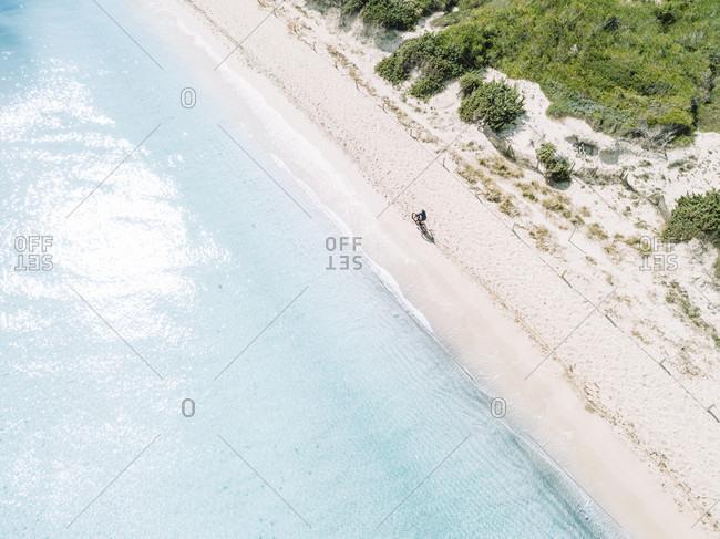Aerial view of cyclists riding mountain bikes on a white sand beach, Mallorca, Balearic Islands, Spain