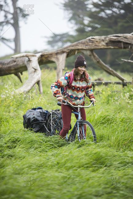 Young adult woman riding on bike through grassy area towing small trailer, Santa Cruz, California, USA