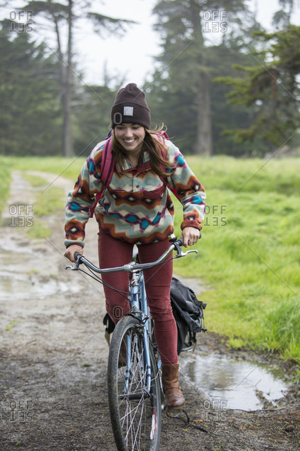 Young adult woman riding on bike through grassy area towing small trailer, ?Santa Cruz, California, USA