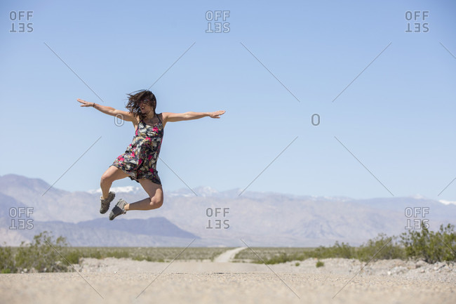 Adult woman in dress jumping into air on remote road in Death Valley National Park, Death Valley, California, USA