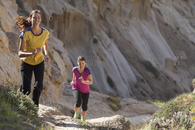 Two women running in sandstone area near Torrey Pines State Park in La Jolla, San Diego, California, USA