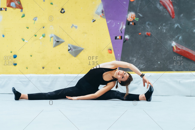 Young woman stretching indoor climbing gym - sport, athletic, fitness concept