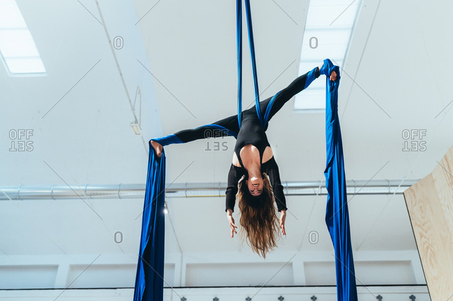 Young woman aerial acrobat hanging wrapped in silk rope - acrobat, circus, active lifestyle concept
