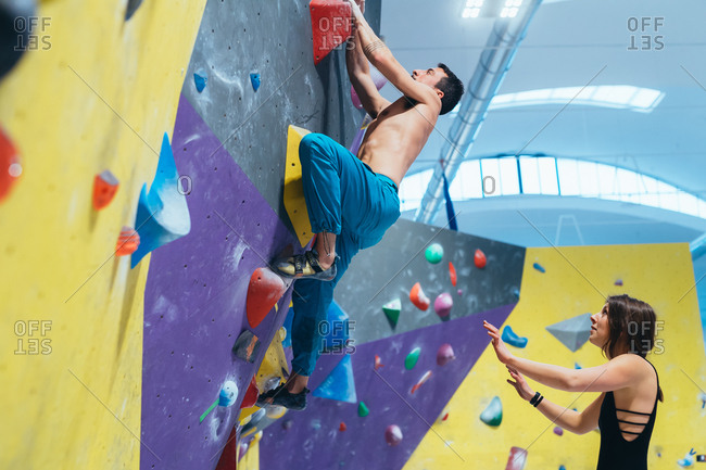 Young woman preparing herself in a climbing gym - preparation, concentration, sportive concept