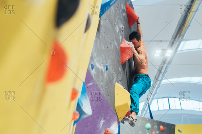 High angle view young adult woman posing in a climbing wall gym looking camera - well being, healthy lifestyle, sportive concept