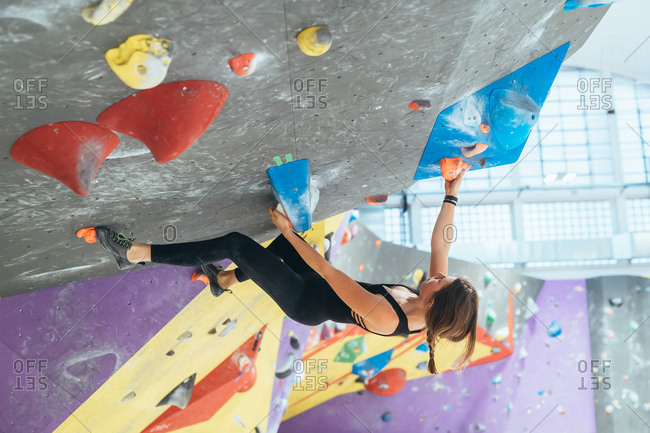 Two young women climbing rock wall indoor - healthy lifestyle, sport, climbing concept