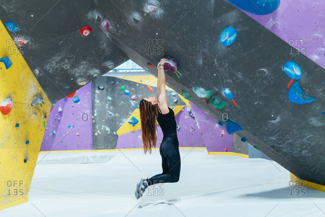 Young adult man and woman posing in a climbing wall gym looking camera - well being, healthy lifestyle, sportive concept